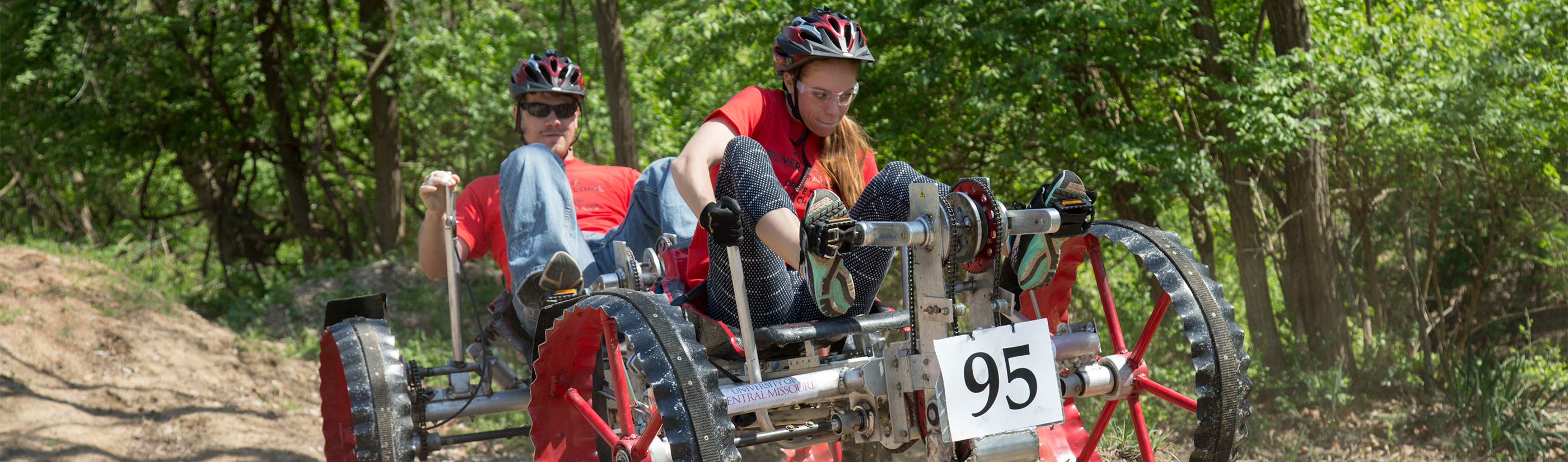 Two students are riding through the woods on a four-wheeled vehicle built as a class project.
